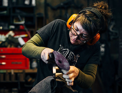 A blacksmithing apprentice grinds away imperfections on a commissioned piece.