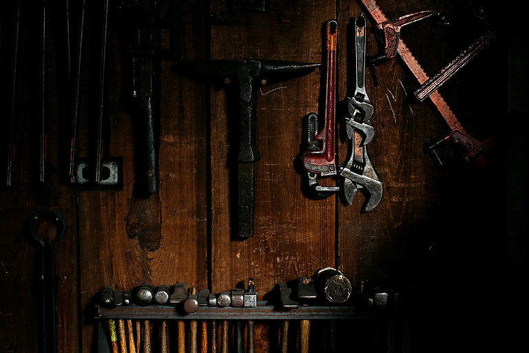 Hammers, wrenches, and various other tools hanging on a wall with wood paneling.