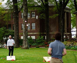 An image of people playing a game of corn hole on the Museum grounds.