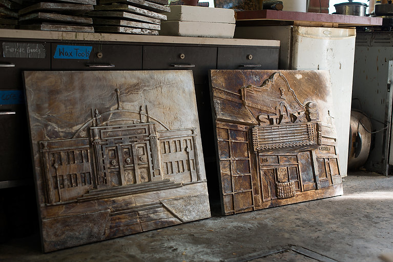 Two large cast plaques that depict buildings from the city of Memphis.