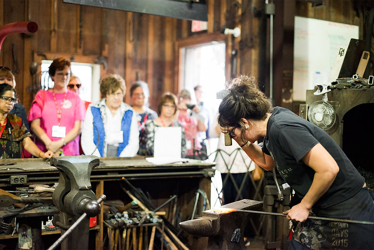 Blacksmithing apprentice Ann Klicka gives a demonstration to a crowd of onlookers in the Smithy.