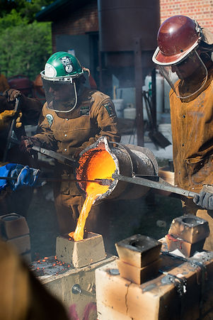 Two foundry artists in protectuve gear pour molten iron into a mold.