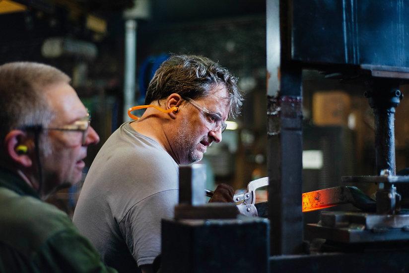 Two blacksmiths hold a glowing hot steel bar in a hydraulic press.