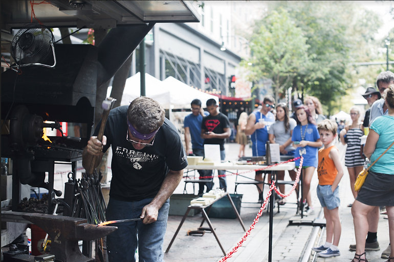 A blacksmith forges in front of a crowd during a vendor fair.