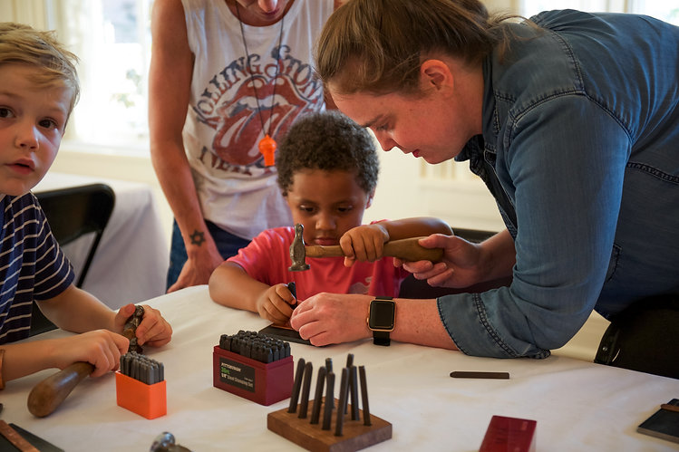 An instructor guides a young child through the process of stamping copper sheet.