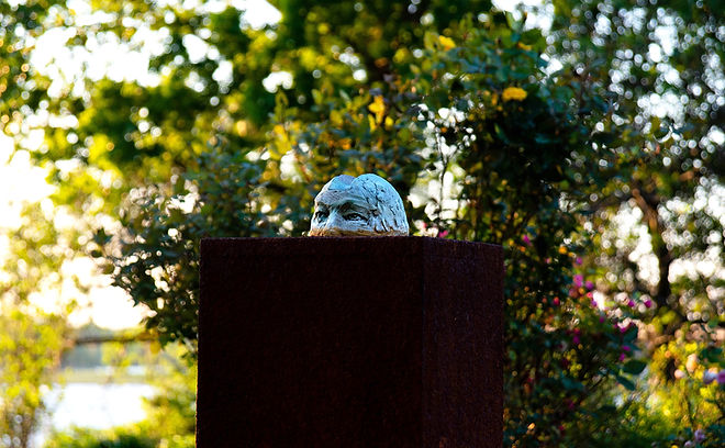 A sculpture of a man's head rising from a rust-colored metal block.