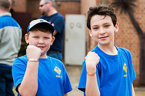 An image of two boys showing the stamped copper bracelets they have made at the Metal Museum.