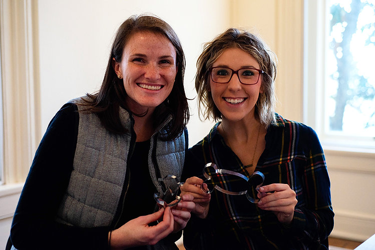 Two girls smile and hold handmade cookie cutters that they created during a class.