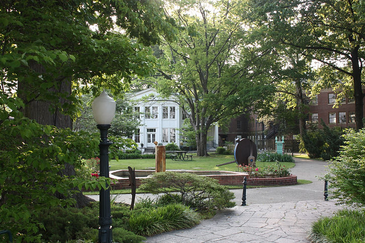 The white, two-story Library building surrounded by lush trees, sculpture, a fountain, and picnic tables.