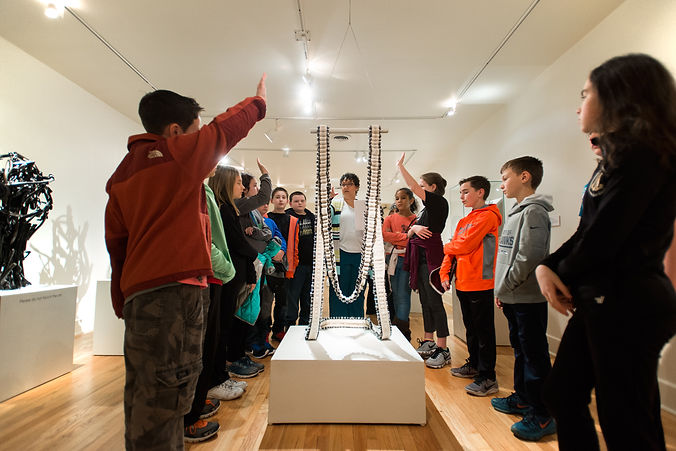 A group of young students in a gallery raise their hand to ask the tour guide a question.
