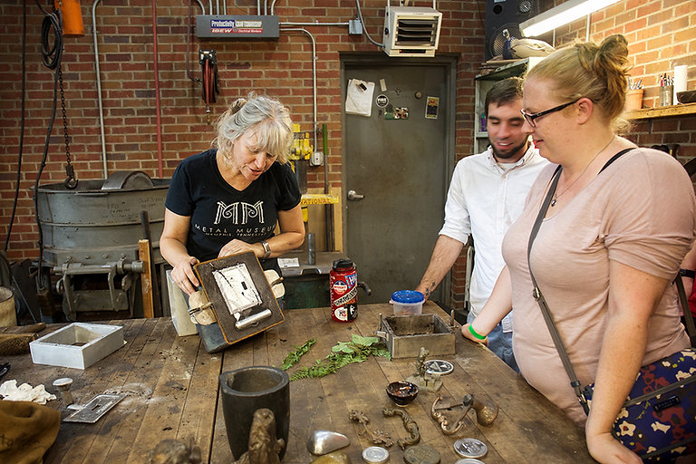 An artist shows visitors a green sand mold in the Museum Foundry.
