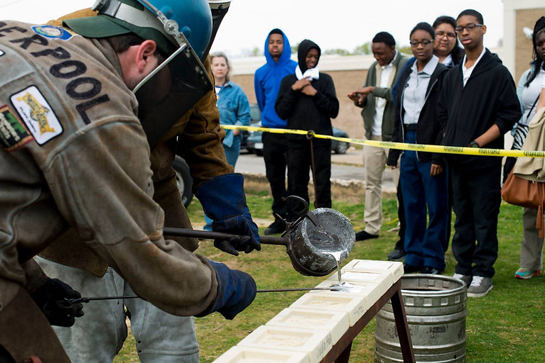 Two foundry artists pour molten aluminum in front of a group of high school students.