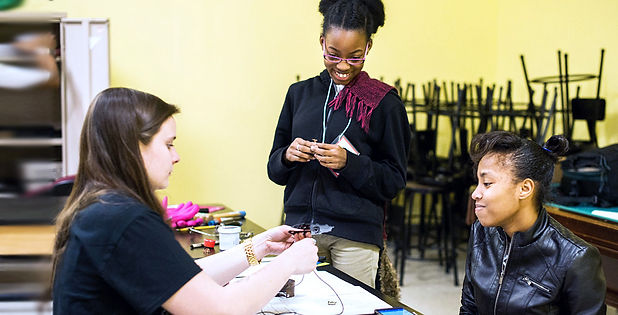 Soulsville students watch an instructor demonstrate a jewelry making technique.