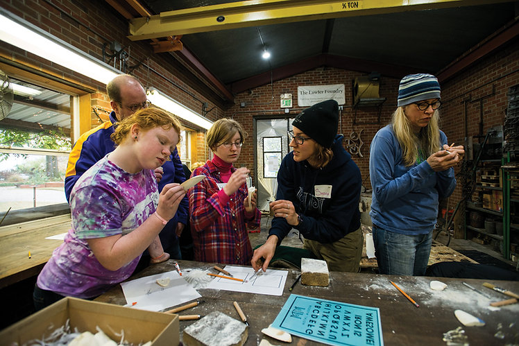 A Museum artist interacts with a group of four family members in the Foundry.