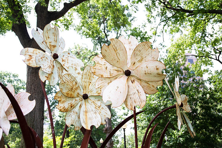 A large dogwood flower sculpture made out of metal.