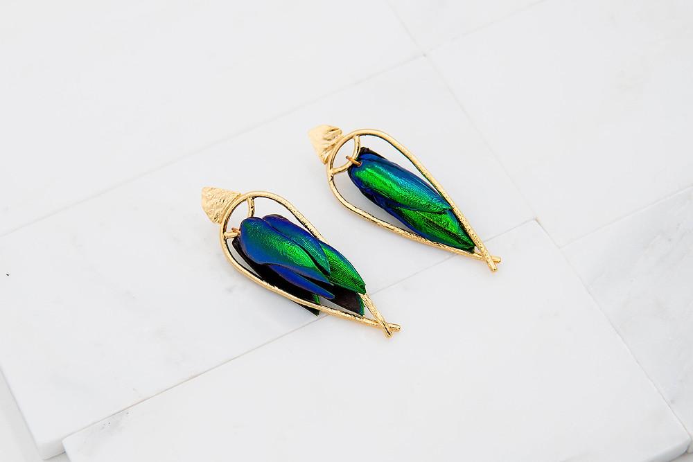 A pair of beetle wing earrings, featuring vibrant blue-green beetle wings encased in a gold upside down teardrop frame.