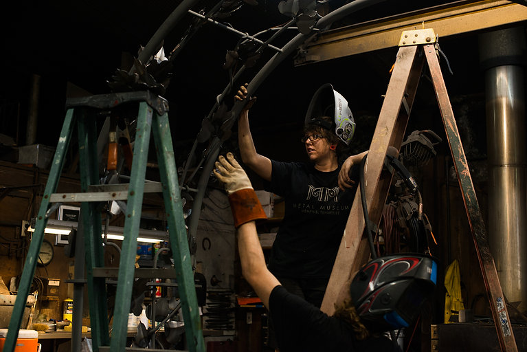 A female blacksmith rests her hand on a large forged and fabricated archway in the Metal Museum's Blacksmith Shop.