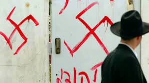 A Jewish man passes anti-Semitic graffiti sprayed on a synagogue in Israel