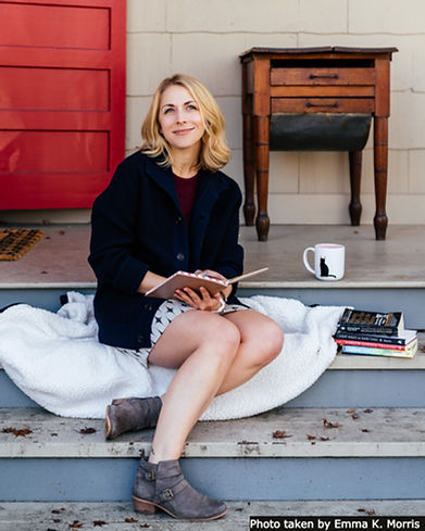 Jenna Sanders, a white woman with shoulder length blonde hair, sits on cream blanket on gray steps. She wears a black sweater and tan patterned skirt with gray ankle boots. She holds a notebook and sits next to a stack of books and coffee mug.