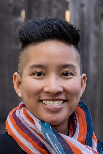 Stephanie Der, a woman with brown skin, brown almond shaped eyes, and short black hair smiles while wearing an orange, purple, turquoise and white striped scarf and small, stud earrings.