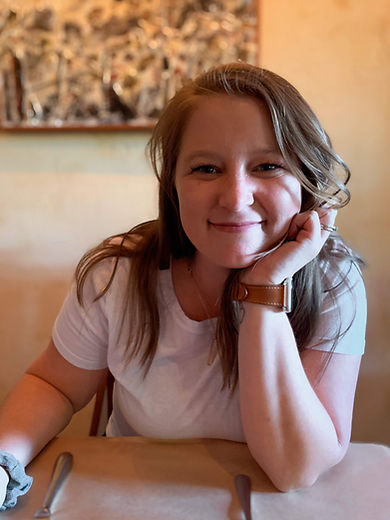 Nicole Driscoll, a white woman with long brown hair, wears a white t-shirt and brown leather wrist watch. She smiles with a closed mouth while leaning on her hand propped on a table.