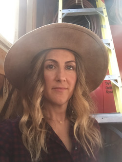A white woman with long, curly blonde hair wears a wide-brimmed tan hat and looks into the camera