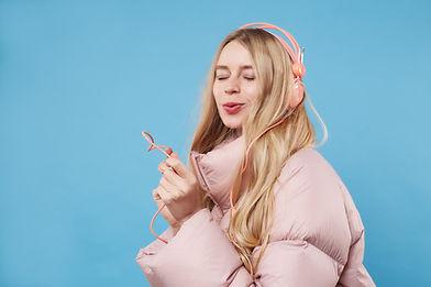Una mujer con abrigo rosa y auriculares