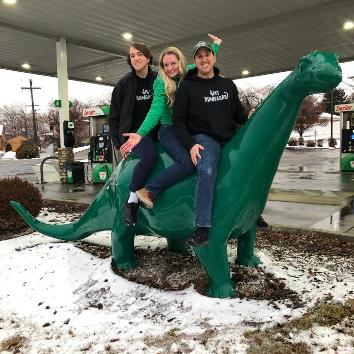 Three people sitting on a Sinclair dinosaur at a gas station.
