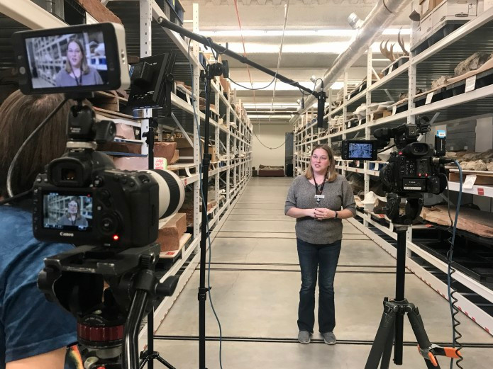 Camera equipment pointed at woman in fossil warehouse
