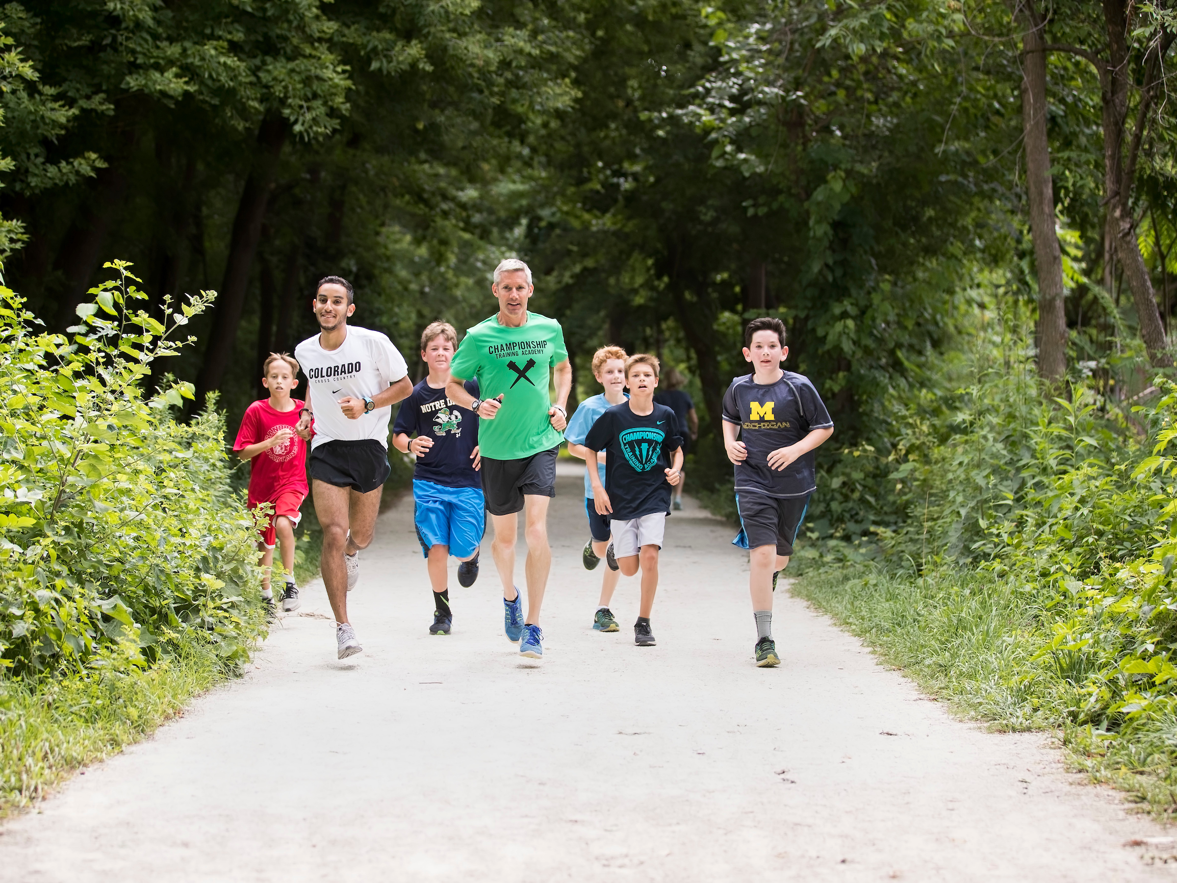 Collegiate runner Ammar Moussa running with the campers