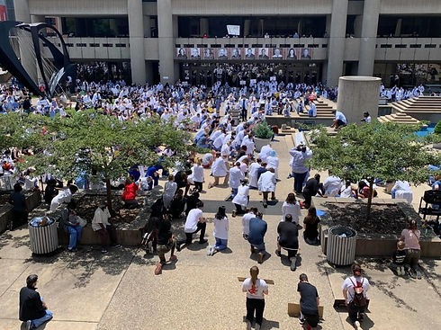 The University of Louisville School of Medicine medical community kneel during the White Coats for Black Lives Rally