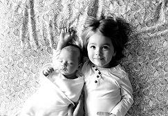 newborn baby laying next to smiling toddler older sister