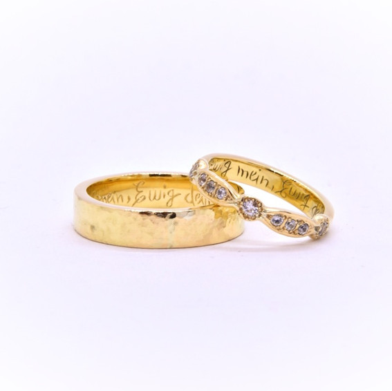 "18k Yellow Gold Rings: 5mm wide hammered texture for him & 3mm wide for her, set with white sapphires. Inside hand engraved: ""Ewig mein, Ewig dein"""