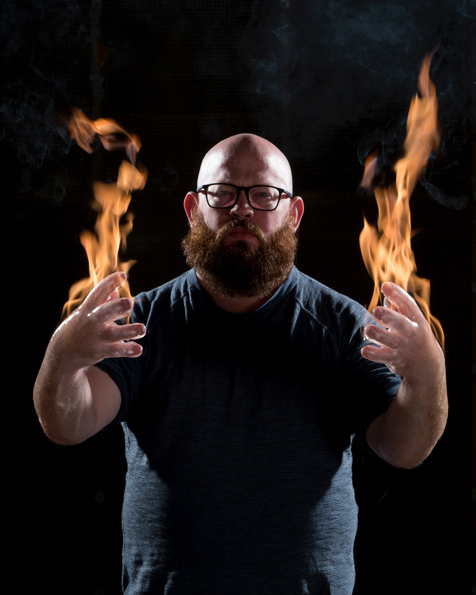 Picture of a bearded man with glasses, with fire rising from his palms