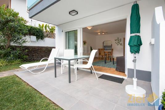 Gartenterrasse mit Esstisch und Liegestuhl