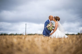 Bride andGroom kissing in a cornfield by Lancashire based professional wedding photographer Jon Boriss