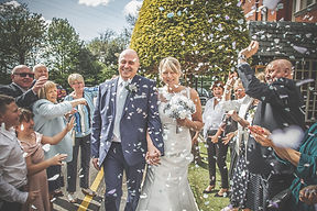 Bride and Groom in confetti by Lancashire based professional wedding photographer Jon Boriss