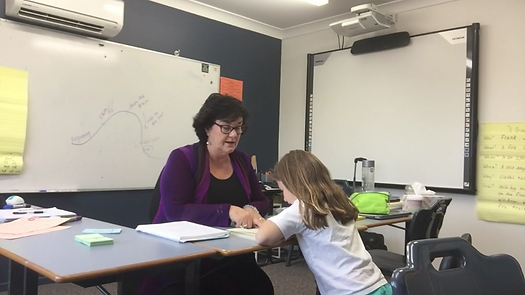 Photo of a teacher helping a student with reading