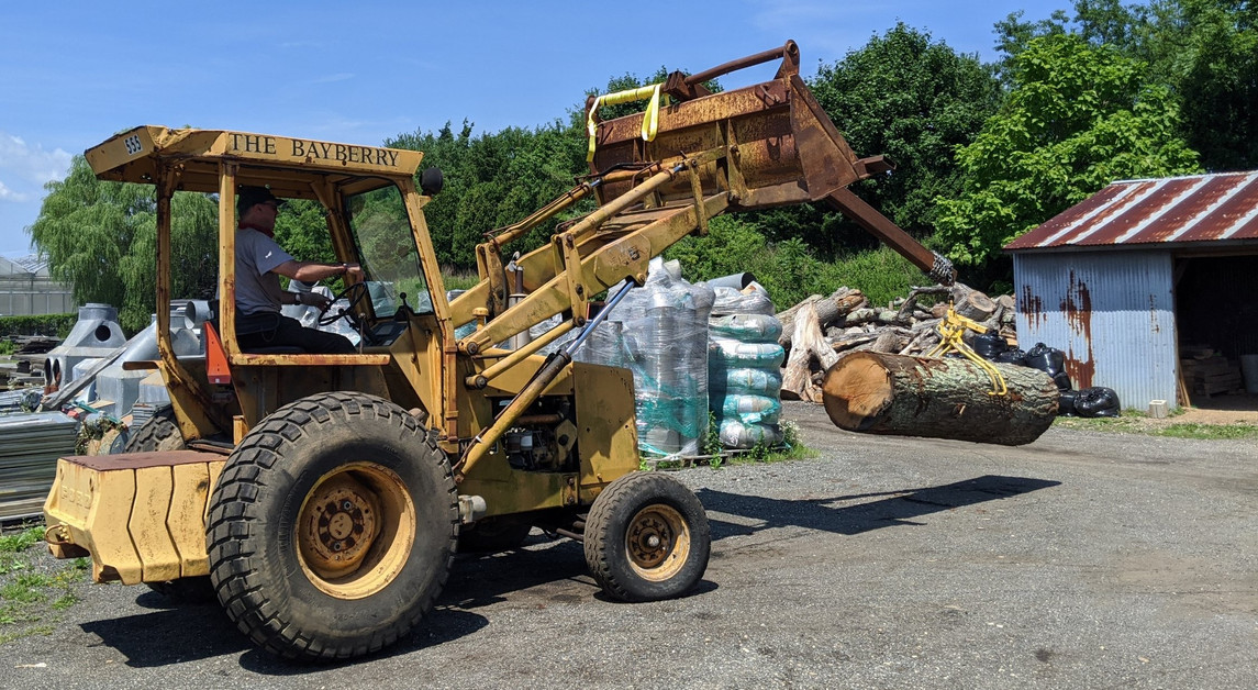 Tim Walz hauling a log with their Ford 555 loader