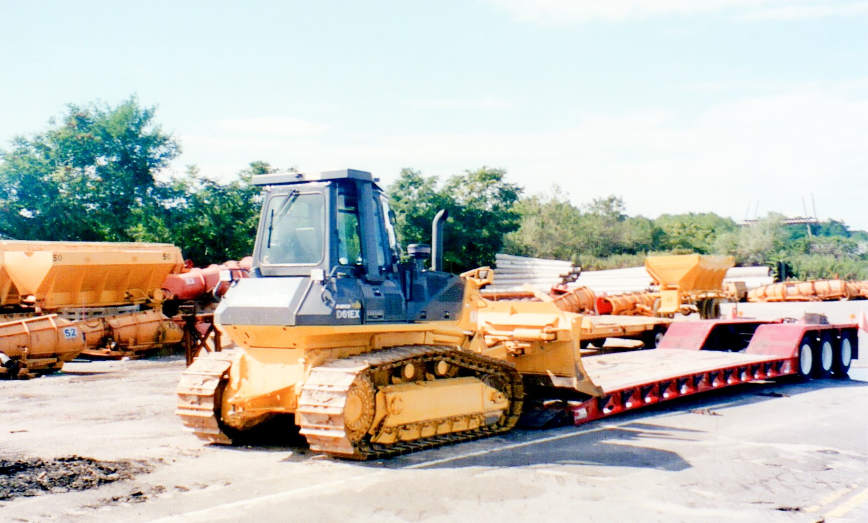 Komatsu D61EX dozer and a 2005 Rogers loboy trailer, parked next to the sand and salt spreaders.