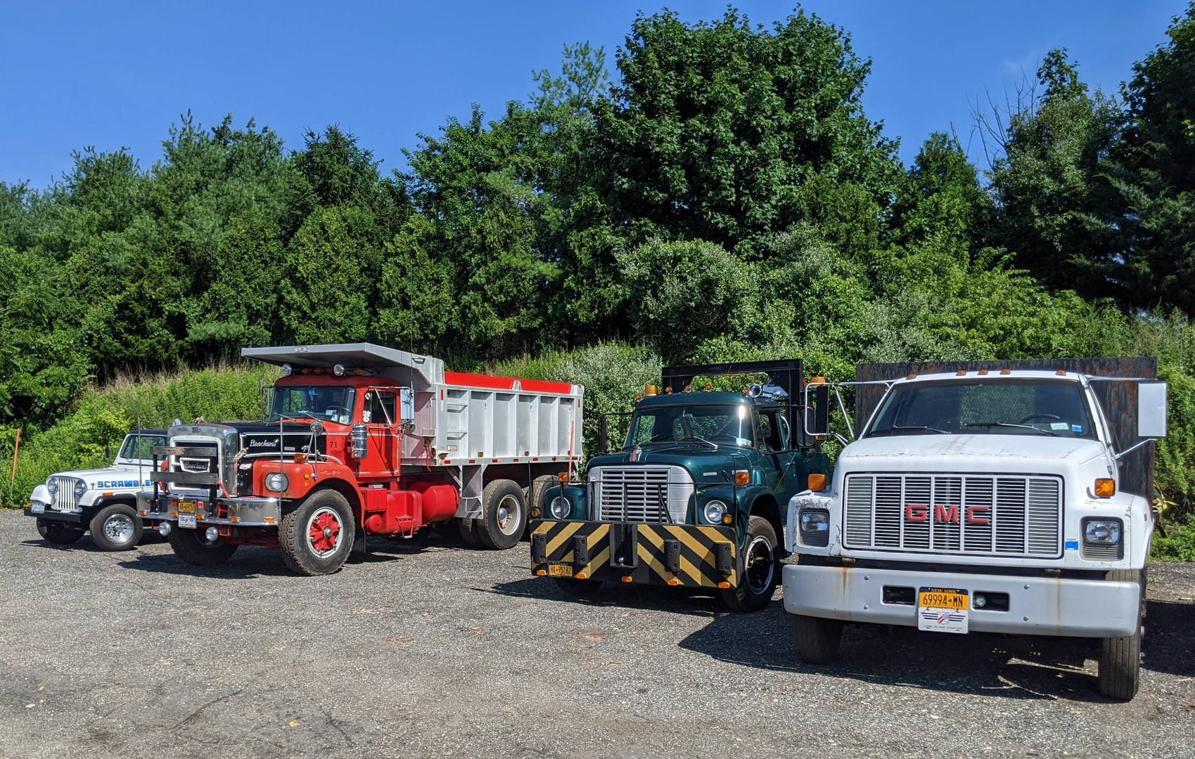 Left to right: Philip Huntington's 1984 AMC Jeep CJ-8 Scrambler pickup, Howard Pratt's 1971 Brockway N361LL dump, Craig Kenda's 1972 International Loadstar wrecker, and Karl Walz Sr.'s 1994 GMC TopKick flatbed