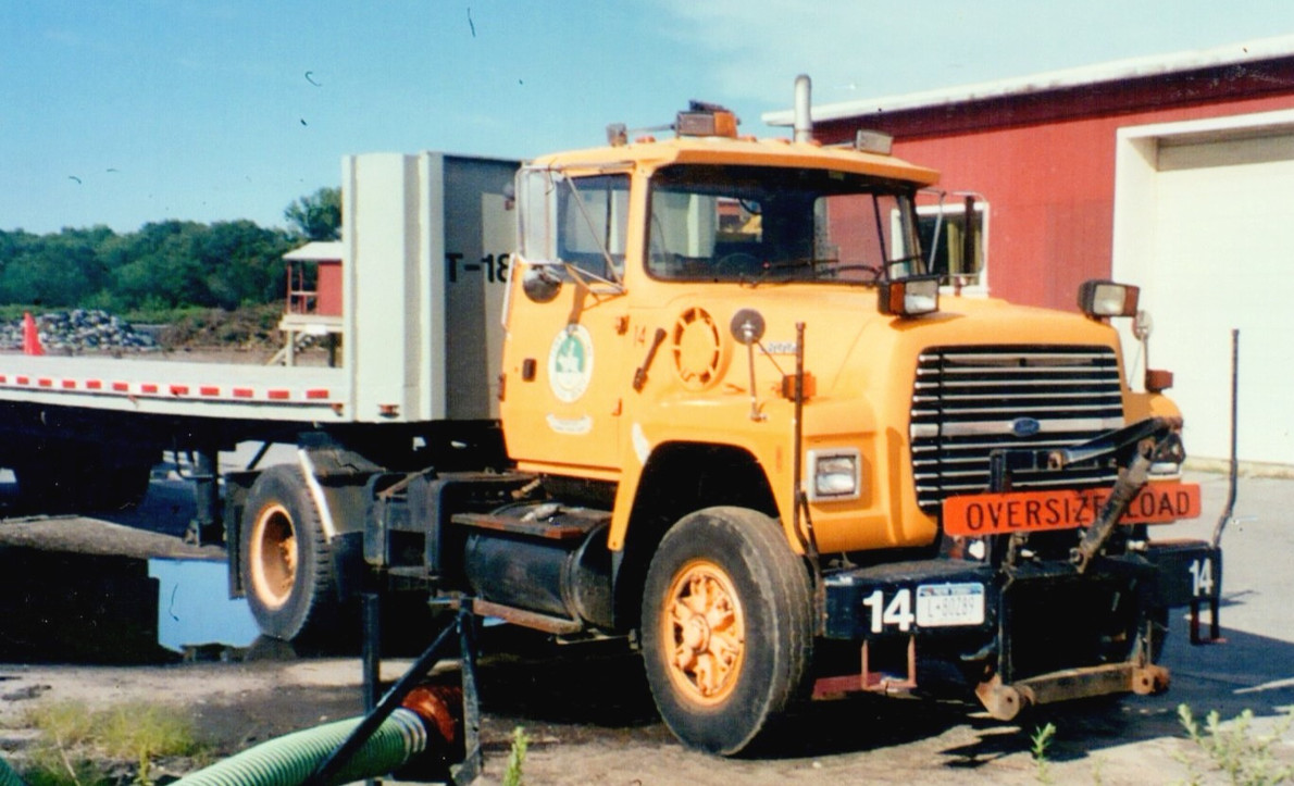 1995 Ford L-8000 tractor with 1977 Stric flatbed trailer, assigned to Denis at one time.