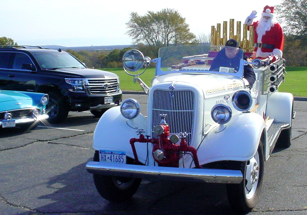 Floyd Chivvis in his 1935 Ford fire engine arriving with Santa