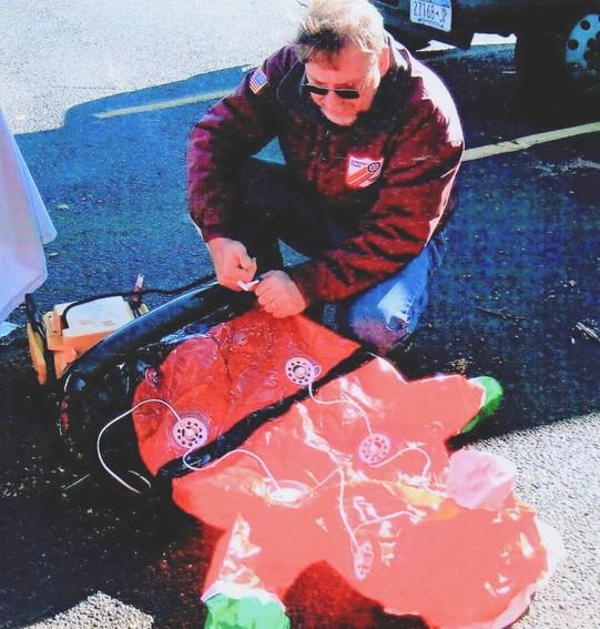 Chapter president Denis Ryan inflating Santa