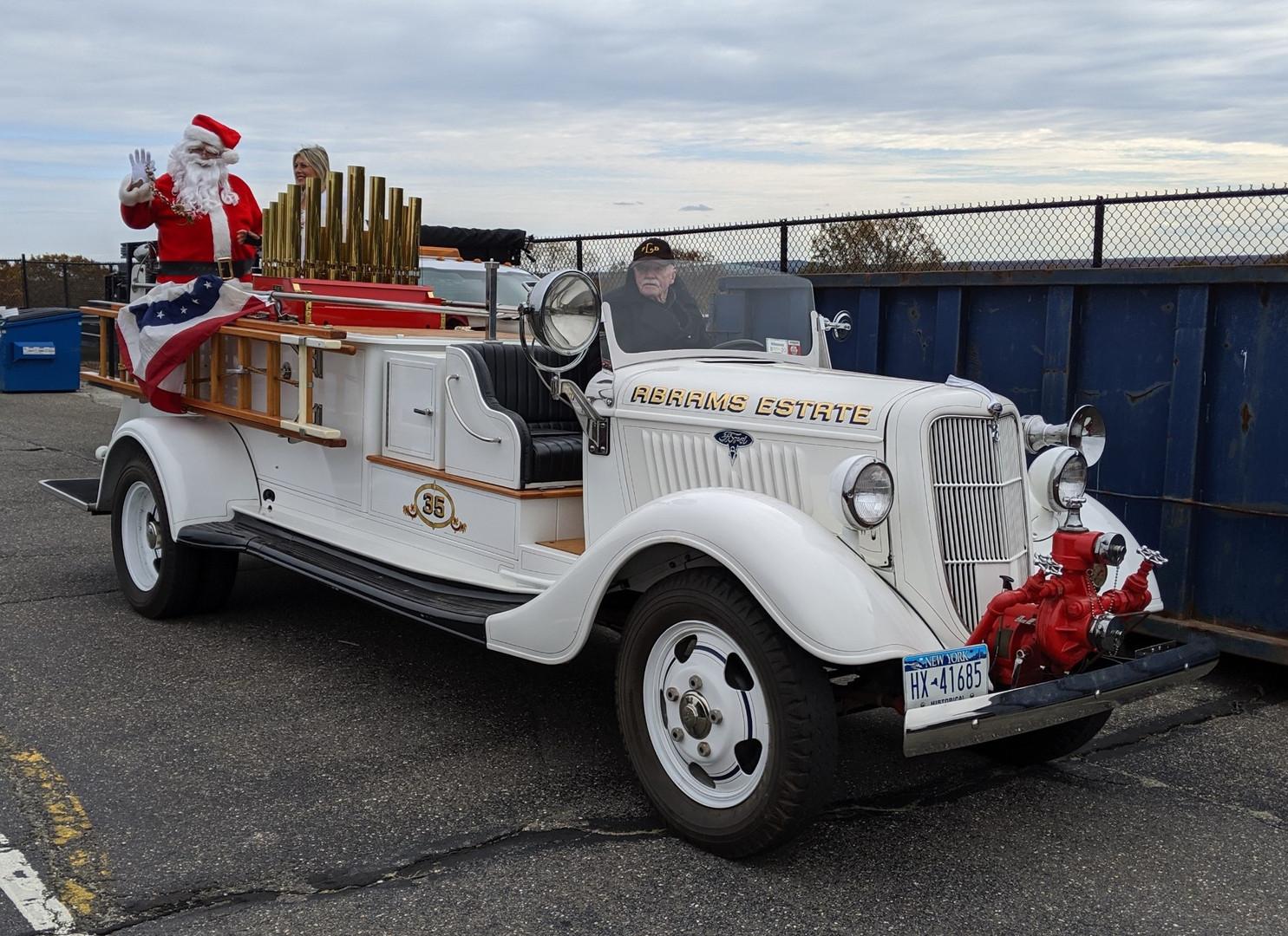 "Floyd Chivvis in his 1935 Ford bringing in Santa & ""Santa's Daughter"""