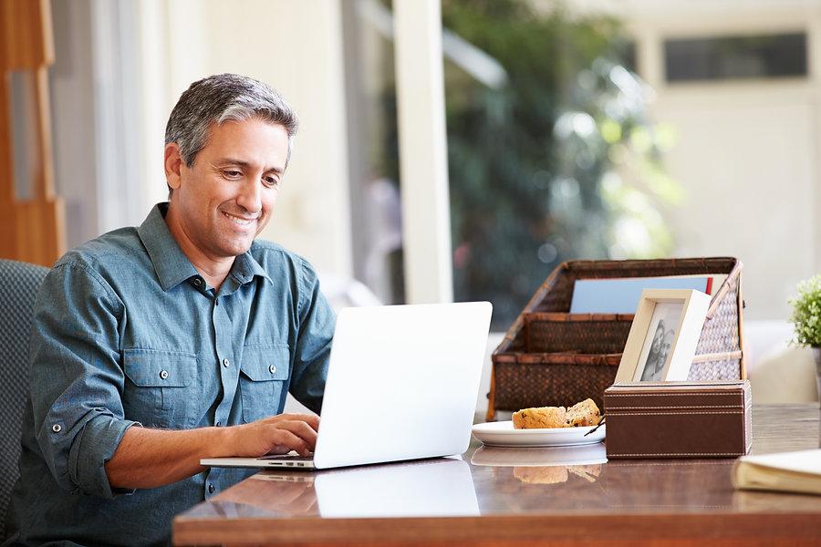 Mature Hispanic Man Using Laptop On Desk