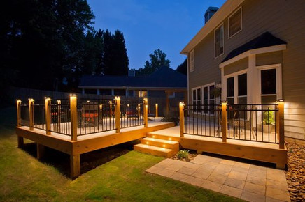 Metal railings are grounded by illuminated wooden pillars, creating a warm glow on this cozy deck space.