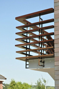 Industrial-style rods are surrounded by a stacked wood railing, creating a modern appeal on this elevated deck.