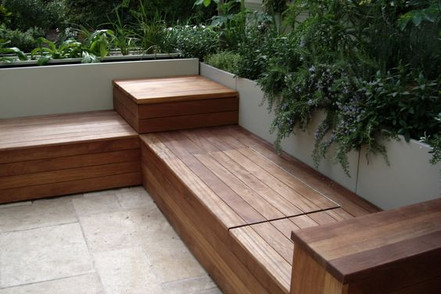 A custom deck features intuitive built-in seating, framed by white stone planters that serve as a rail.