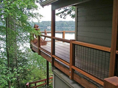 A contemporary lake house is elevated with a warm and rustic deck railing, complete with black hog wire.
